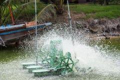 wässern Sie die Turbine, die im Teich arbeitet und lassen Sie Wasserspritzen herein O addieren Stockfotografie