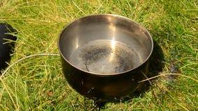 Wässern Sie in einer Kasserolle auf Feuer draußen kochen stock video