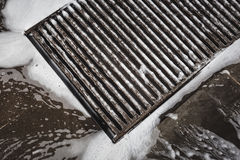Wässern Sie Entwässerungsgrill auf der Waschanlage, den Schaum, der in die Wanne fließt lizenzfreies stockbild