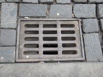 Wässern Sie Entwässerungsloch mit Gitter auf einer Pflasterstraße Lizenzfreie Stockbilder
