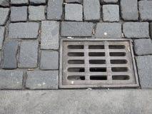 Wässern Sie Entwässerungsloch mit Gitter auf einer Pflasterstraße Stockfoto