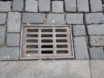 Wässern Sie Entwässerungsloch mit Gitter auf einer Pflasterstraße Lizenzfreies Stockbild