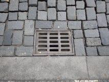Wässern Sie Entwässerungsloch mit Gitter auf einer Pflasterstraße Stockfotos