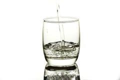 Wässern Sie gegossen werden in eine Glasschale Stockfotos