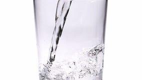 Wässern Sie gegossen werden in Glas gegen weißen Hintergrund, stock video