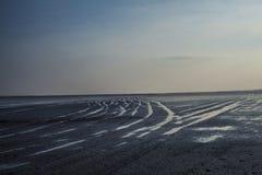 Wässern Sie Gezeitenbahnen auf sandigem Strand bei Sonnenuntergang Lizenzfreies Stockbild