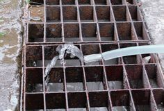 Wässern Sie Klempnerarbeit im Gummiplastikband mit dem Fließen auf Abzugsgraben Lizenzfreie Stockbilder