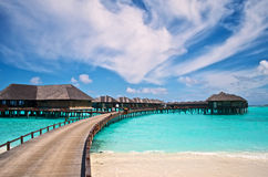 Wässern Sie Landhäuser und hölzerne Anlegestelle des Erholungsortes in den Malediven stockfotos