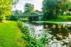 Wässern Sie Landschaft mit einem Fluss-, Brücken- und Grasrasen Stockfoto
