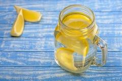 Wässern Sie mit einer Zitrone auf einem hölzernen Hintergrund Stockbild