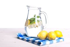 Wässern Sie mit Zitrone und Minze in einer Seitenansicht des Glases auf dem Tisch von i Lizenzfreie Stockfotos