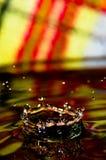 Wässern Sie Spritzen in der Farbe mit einem Tropfen des Wassers Stockfotografie