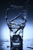 Wässern Sie Spritzen in einem Glas des Eiswürfelfallens lizenzfreie stockfotografie