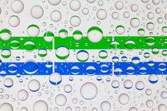 Wässern Sie Tropfen auf Glas und Flaggen des Sierra Leone lizenzfreie stockfotos