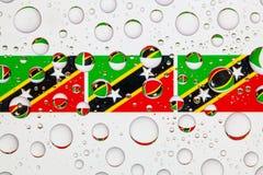 Wässern Sie Tropfen auf Glas und Flaggen des St. Kitts und Nevis Lizenzfreies Stockbild