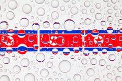 Wässern Sie Tropfen auf Glas und Flaggen von Nordkorea lizenzfreie stockfotos