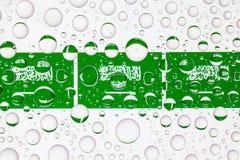 Wässern Sie Tropfen auf Glas und Flaggen von Saudi-Arabien stockfoto