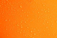 Wässern Sie Tropfen auf orange Hintergrund, Abschluss oben Lizenzfreies Stockbild