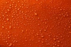 Wässern Sie Tropfen auf orange Hintergrund, Abschluss oben Stockbilder