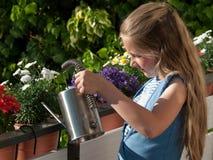 Wässernblumen des Mädchens Stockfoto