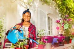 Wässernde eingemachte Blumen des schönen afrikanischen Mädchens lizenzfreies stockfoto