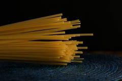 Włoskiego spaghetti surowy makaron, ciemny tła czerń i głęboki błękit, zdjęcie stock