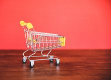 Wózek na zakupy na drewnianym, Online robić zakupy Black Friday pojęcie z żółtym wózkiem na zakupy na czerwieni/ zdjęcia royalty free