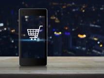 Wózek na zakupy ikona na nowożytnym mądrze telefonu ekranie na drewnianym stole Zdjęcie Royalty Free