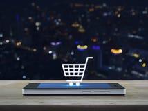Wózek na zakupy ikona na nowożytnym mądrze telefonu ekranie na drewnianym stole Obrazy Stock