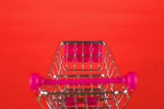 Wózek na zakupy lub supermarketa tramwaj na czerwonym tle, biznes Obraz Royalty Free