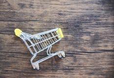 Wózek na zakupy na nieociosanym drewnianym tle, Online robić zakupy czarnego Piątku pojęcie/ zdjęcia stock