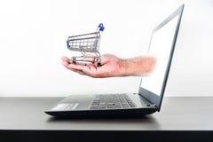 Wózek na zakupy w ręka Komputerowego notatnika pustym ekranie fotografia royalty free