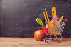 Wózek na zakupy z szkolnymi dostawami nad chalkboard tłem Obraz Stock