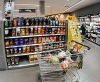 Wózek na zakupy z warzywami obok szerokiego wyboru kawa Obraz Stock