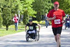 Wózka inwalidzkiego mężczyzna biega wśród przyrodniego maratonu Ryazan Kremlin dedykujący rok ekologia w Rosja Obraz Royalty Free