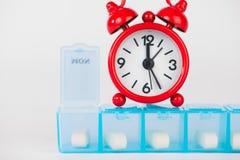 Wöchentlicher Pillenkasten und rote Uhr zeigen Medizinzeit Lizenzfreie Stockfotos