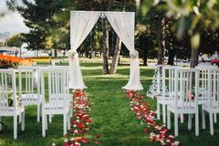 Wölben Sie sich für die Hochzeitszeremonie, verziert mit Stoff und Blumen lizenzfreies stockfoto