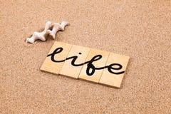 Wörter auf dem Sandleben Stockbild