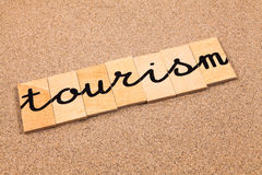 Wörter auf Sandtourismus stockfotografie