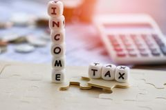 Wörter der Einkommenssteuererklärungs-Abzugs-Rückerstattung Concep/der Steuer auf Laubsägen- und Taschenrechnermünzen auf Rechnun stockfotografie