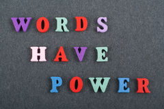 WÖRTER HABEN ENERGIE-Wort auf dem schwarzen Bretthintergrund, der von den hölzernen Buchstaben des bunten ABC-Alphabetblockes ver Stockfotografie