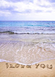 Wörter ICH LIEBE DICH geschrieben auf Sand, mit Wellen in Hintergrund Lizenzfreie Stockfotos