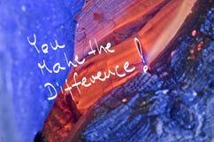 Wörter unterscheiden Sie! handgeschrieben auf hölzernem Hintergrund des roten Brandes Lizenzfreie Stockfotografie