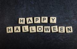 Wühlen Sie Buchstabefliesen auf dem schwarzen Schieferhintergrund, der glückliches Halloween buchstabiert lizenzfreie stockfotos