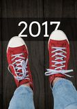 2017 Wünsche des neuen Jahres mit dem Jugendlichen, der rote Turnschuhe trägt Stockfotografie