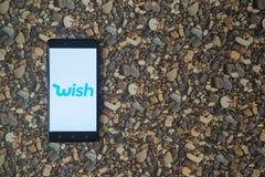 Wünschen Sie Logo auf Smartphone auf Hintergrund von kleinen Steinen Stockbilder