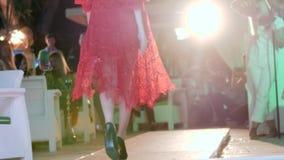Würdevolle Frau im rotem Spitzekleid und -schuhen auf hohen Absätzen gehend am Podium im hellen Licht des Scheinwerfers stock footage