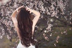 Würdevolle Frau im weißen Kleid, das mit ihr zurück unter blühenden Bäumen arbeiten steht im Frühjahr im Garten Stockbild