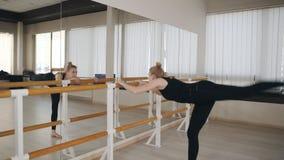 Würdevoller Tänzer des klassischen Balletts in der Sportkleidung, die die Spalte stehend ausdehnt Position an Ballett Barre im Ta stock footage