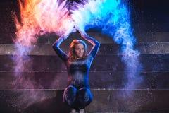 Würfe und Tanz der jungen Frau mit Farbpulver auf dunklem Hintergrund lizenzfreie stockbilder